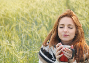 beautiful woman enjoying scent of hot drink in autumn cold day